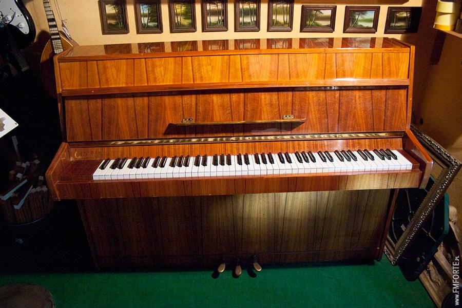 Pianino Calisja widok od frontu. Całe pianino w kadrze. Posiada piękną drewnianą pionową mozajkę.