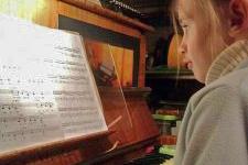 Dziewczynka podczas nauki gry na pianinie